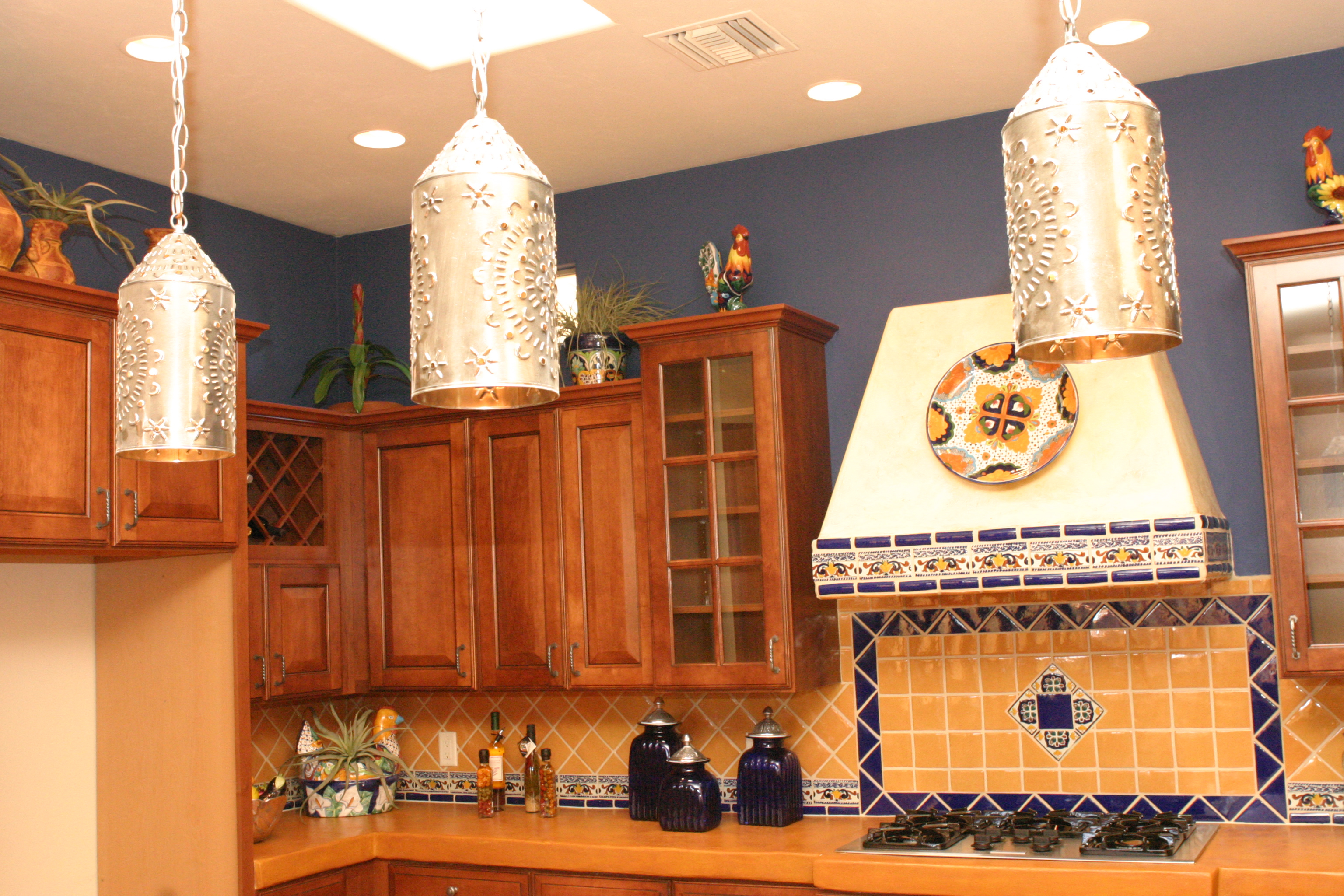 A kitchen with organge and blue tiles on the wall above a granite countertop